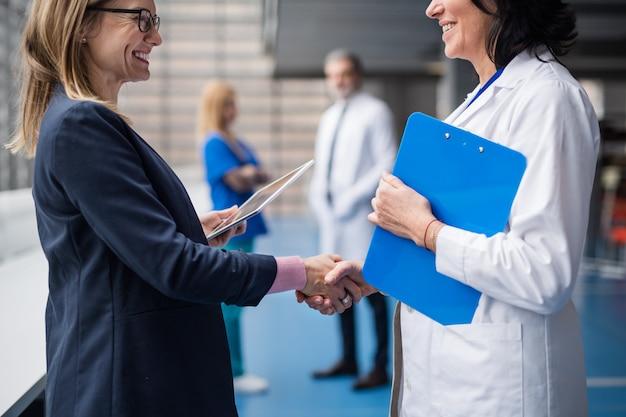 Médico irreconocible hablando con el representante de ventas farmacéuticas, estrechándole la mano.