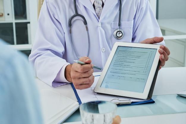 Médico irreconocible que extiende la pestaña digital para que el paciente anónimo complete el cuestionario