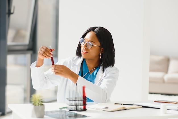 Médico joven hermosa chica afroamericana en una bata blanca con un estetoscopio. sentado en una mesa con matraces de reactivo sobre fondo blanco. asistente de laboratorio femenino estudiando muestras de sangre para su análisis