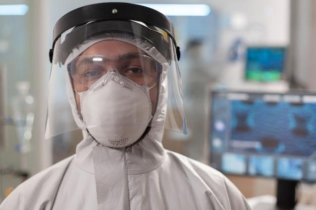 Médico de laboratorio cansado en traje de protección y mirando a cámara