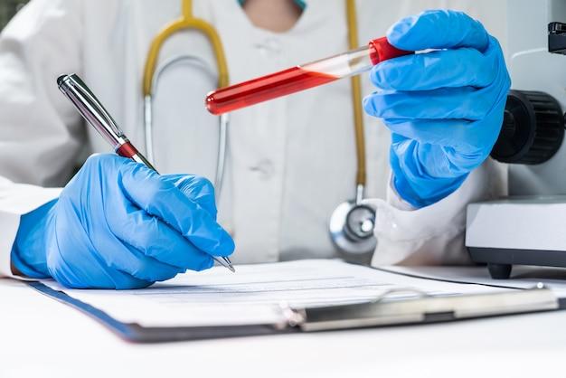 Un médico en un laboratorio sostiene un tubo de ensayo con un análisis de sangre del paciente. registra el diagnóstico en el formulario del paciente