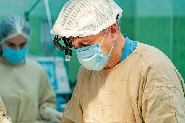 Un médico con una máscara y una bata con un dispositivo médico se encuentra sobre el paciente de una enfermera.