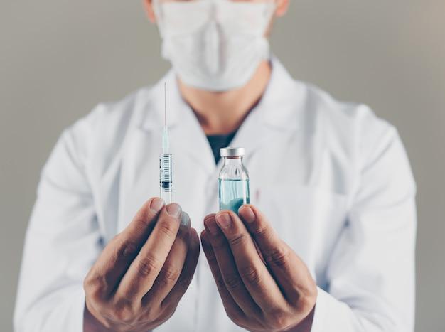 Un médico con máscara con vial y jeringa en sus manos vista lateral