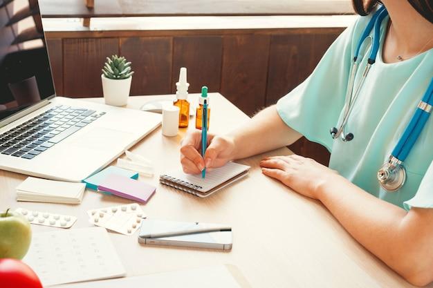 Médico de medicina femenina rellenando el formulario médico del paciente