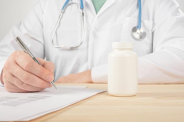 Médico de medicina masculina sujete el frasco de pastillas y escriba la receta al paciente en la mesa de trabajo