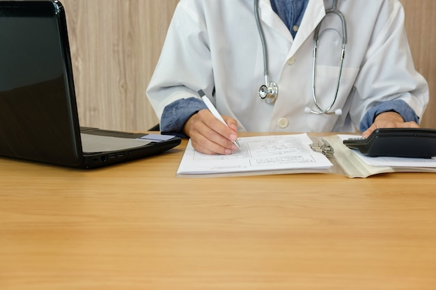 Médico médico con estetoscopio calcula los costos e ingresos de la tarifa médica.