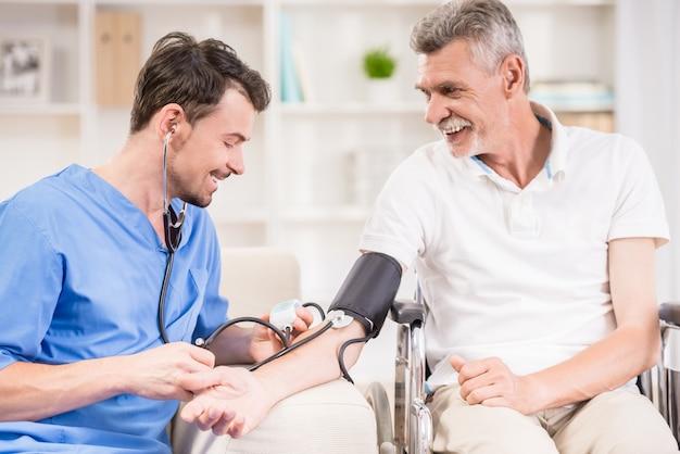 Médico medir la presión arterial al paciente mayor.