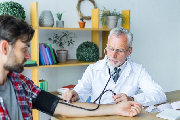 Médico medir la presión arterial del paciente joven
