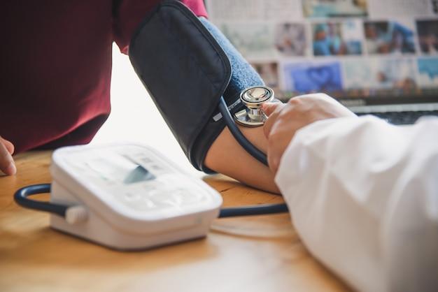 Médico medir la presión sanguínea de su paciente