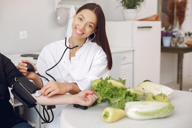 Médico mide la presión del paciente en la cocina.