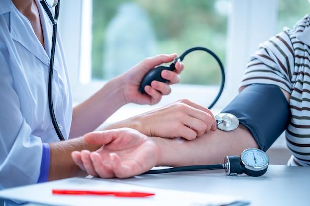 El médico mide la presión del paciente durante un examen médico y una consulta en el hospital.