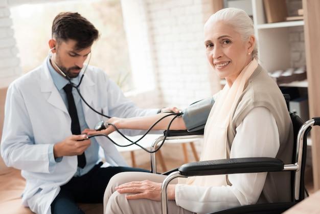 El médico mide la presión del viejo paciente.