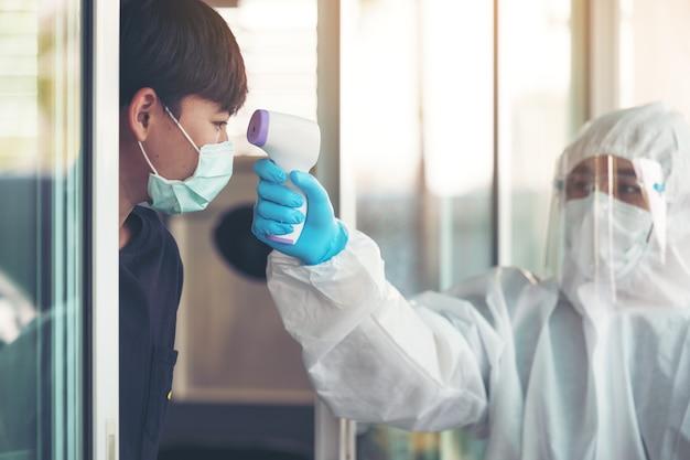 Médico midiendo la temperatura con un nuevo termómetro digital para una paciente durante la pandemia del virus corona
