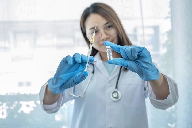 Médico de la mujer asiática que sostiene la botella y la jeringa de la vacuna.