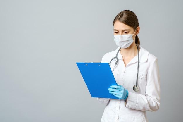 Médico de la mujer joven con el estetoscopio que prescribe el tratamiento al paciente. doctora con pluma escribiendo recetas en el portapapeles. aislado en gris