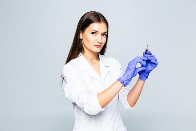 Médico de la mujer joven con una jeringuilla en su mano en la pared blanca.
