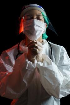Médico mujer reza para poner fin a la epidemia