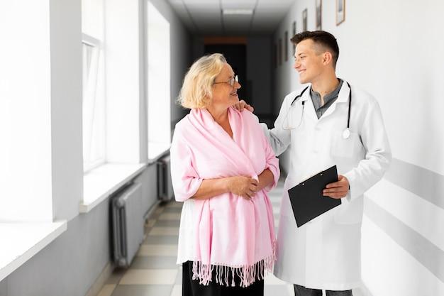 Médico y mujer senior mirando el uno al otro