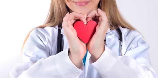 Médico mujer sosteniendo un corazón rojo