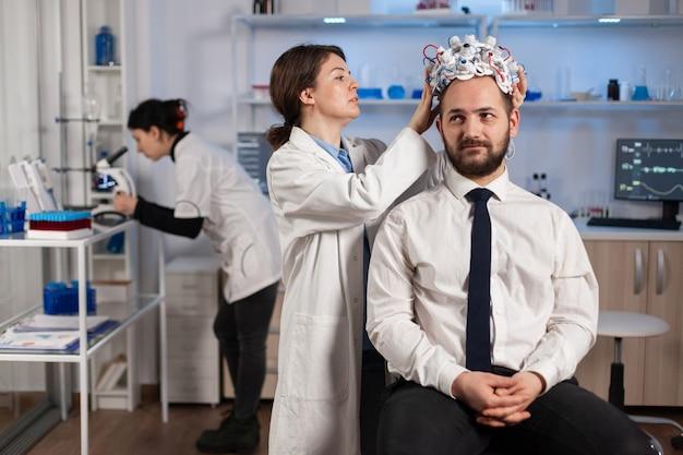 Médico neurólogo que analiza el cerebro del hombre y el sistema nervioso mediante auriculares de exploración de ondas cerebrales. investigador que utiliza alta tecnología en desarrollo de innovación neurológica que monitorea los efectos secundarios en la pantalla del monitor
