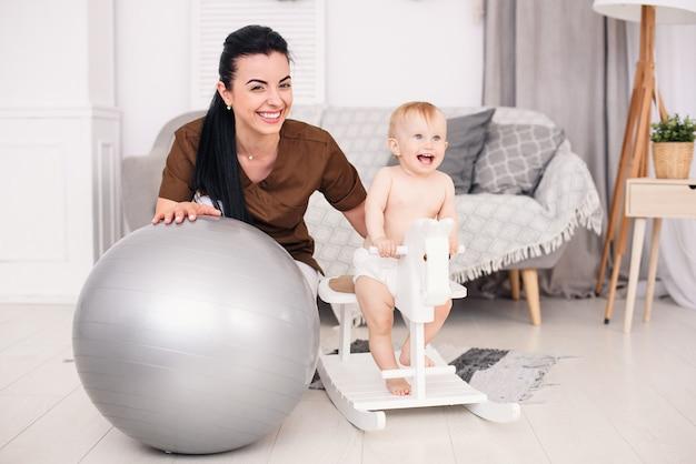 Médico de niños amable y amigable jugando con niña. pequeño bebé sonriente que juega en un caballo de juguete de madera en sitio acogedor.
