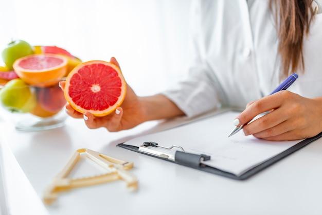 Médico nutricionista escribiendo historia clínica en la oficina.