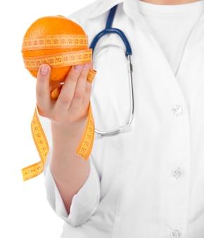 Médico nutricionista con fruta y cinta métrica, aislado en blanco