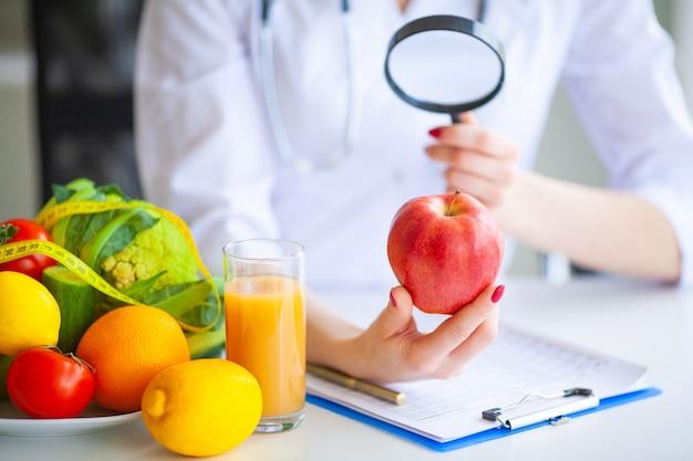 Médico nutricionista mantenga manzana roja en su oficina.