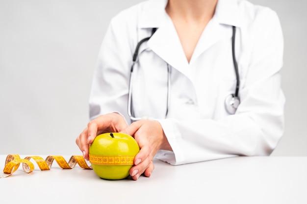 Médico nutricionista midiendo una manzana