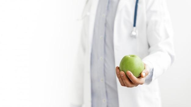 El médico nutricionista sostiene manzana
