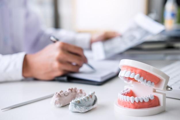 Médico o dentista que trabaja con la radiografía del diente del paciente, el modelo y el equipo utilizado en el tratamiento.