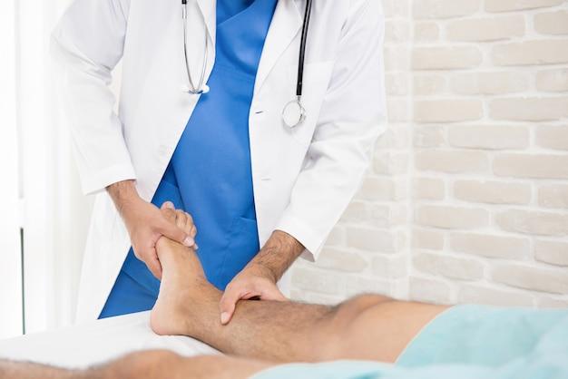 Médico o fisioterapeuta que da tratamiento al paciente con una pierna rota.