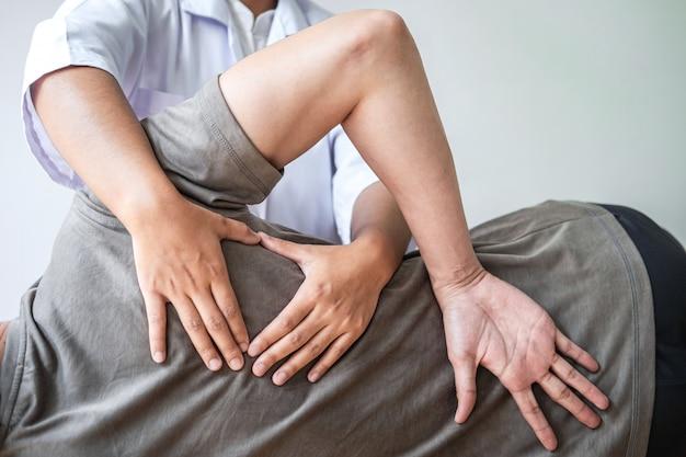 Médico o fisioterapeuta trabajando examinando el tratamiento de la espalda lesionada del paciente masculino atleta, haciendo la terapia de rehabilitación del dolor en la clínica