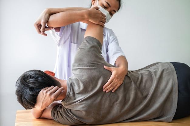 Médico o fisioterapeuta trabajando examinando el tratamiento de la espalda lesionada del paciente masculino atleta