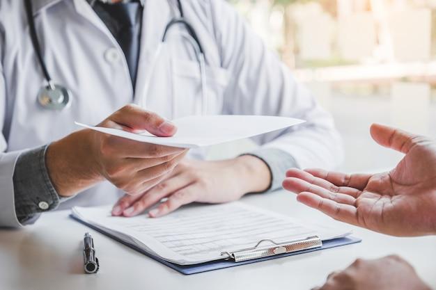 Médico o médico escribiendo un diagnóstico y dando una receta médica al paciente masculino