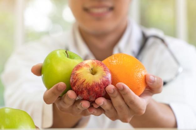 Médico o nutricionista con fruta fresca y sonrisa en clínica.