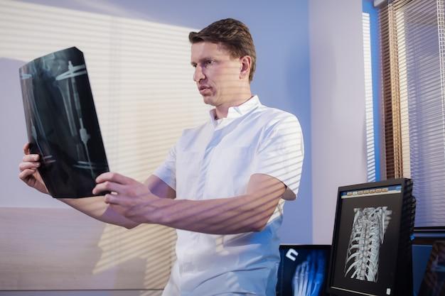 El médico observa la radiografía del paciente.
