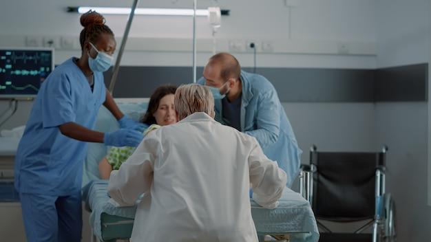 Médico obstetra y enfermera afroamericana que entrega a un niño