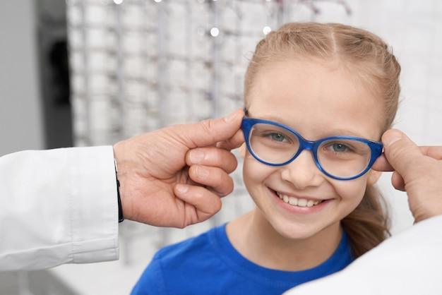 Médico oftalmólogo ayudando a la niña a elegir anteojos.
