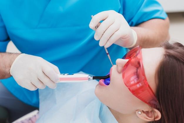 El médico ortodoncista examina al paciente después de cepillarse los dientes.