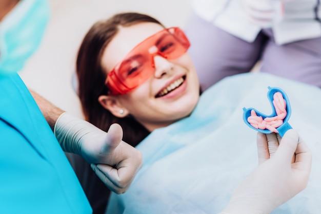 El médico ortodoncista realiza un procedimiento para limpiar los dientes.