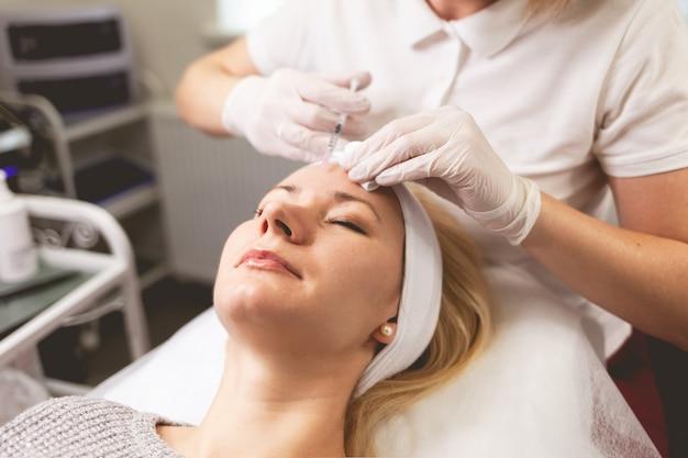 El médico ósmetólogo inyecta botox en la frente del paciente