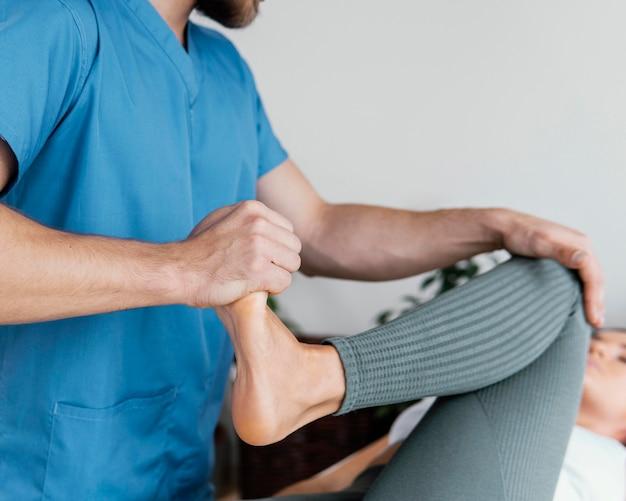 Médico osteópata comprobando el movimiento de la pierna del paciente femenino