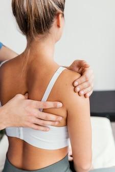 Médico osteópata masculino comprobando la escápula del paciente femenino