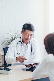 Médico y paciente asiáticos están discutiendo