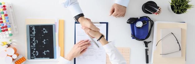 El médico y el paciente se dan la mano en un apretón de manos en el concepto de seguro de medina de mesa médica