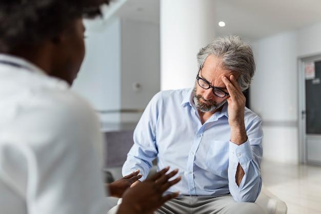 Médico y paciente discutiendo sobre el informe en la sala de espera del hospital