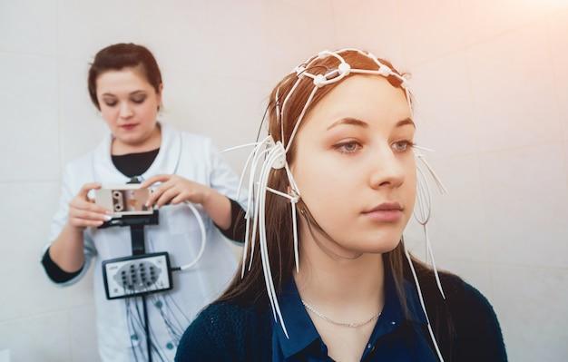 Médico y paciente con electrodo de encefalografía.