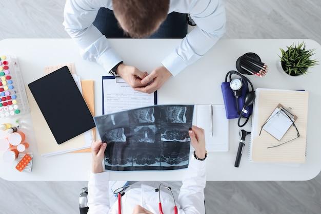 El médico y el paciente están discutiendo la radiografía en la mesa de trabajo