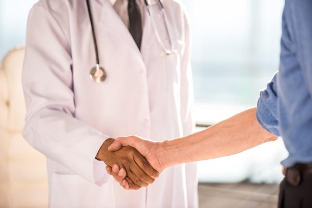 Médico y paciente estrechándole la mano.